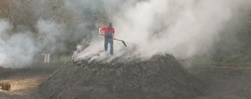 Kulturweg Eisen Holzkohlenmeiler Köhler Reinhold Wagner kontrolliert die Rauchöffnung am Meiler